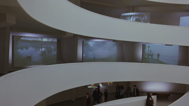 wide angle of people, museum patrons, visitors at guggenheim museum. frank lloyd wright architecture. digital video art exhibits on walls. atrium. - museum stock-videos und b-roll-filmmaterial