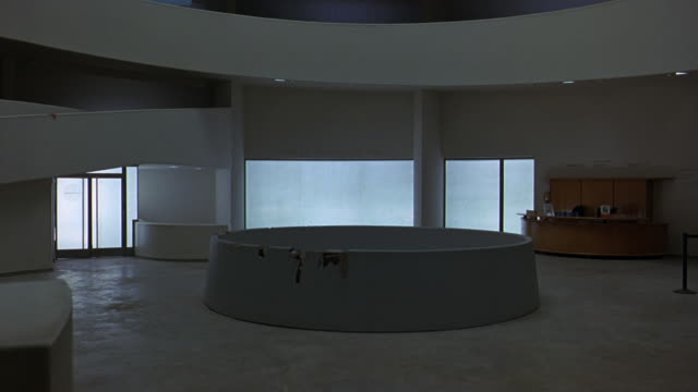 pan right to left of lobby or reception area of guggenheim museum. circular art piece in center. information desks. retractable belt stanchions. ramp or incline, walkway. frank lloyd wright architecture. atrium. digital video art exhibits on walls. - left atrium stock videos & royalty-free footage