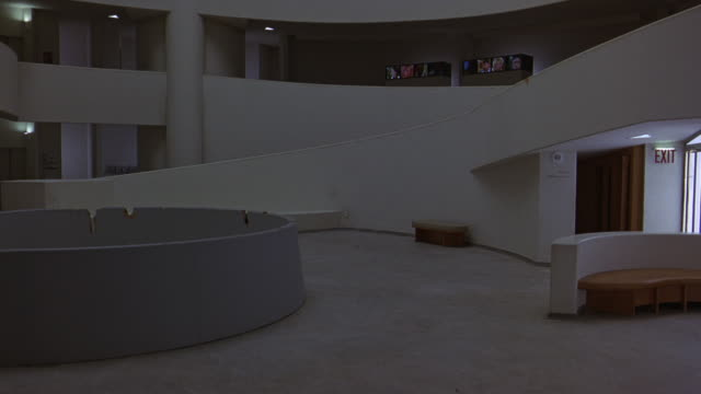 pan right to left of lobby or reception area of guggenheim museum and then up to upper floors, levels. circular art piece in center. information desks. bench. retractable belt stanchions. ramp or incline, walkway. frank lloyd wright architecture. atrium. - left atrium stock videos & royalty-free footage