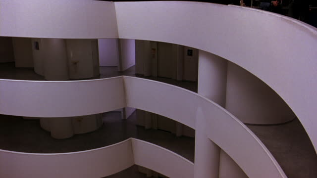 pan left to right of floors or levels in guggenheim museum, then down to lobby on ground floor. information or reception desks. insignia visible. broken sculpture. frank lloyd wright architecture. atrium. digital video art exhibits on walls. - left atrium stock videos & royalty-free footage