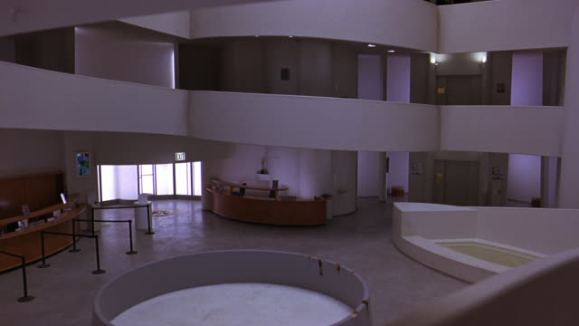pan right to left of lobby or reception area of guggenheim museum. information desks. frank lloyd wright architecture. atrium. digital video art exhibits on walls. - left atrium stock videos & royalty-free footage