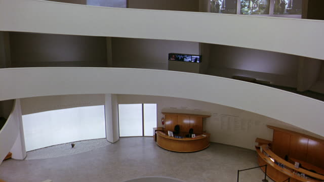 pan right to left of floors or levels of guggenheim museum and then high angle down of lobby.  circular art piece in center. information desks. retractable belt stanchions. ramp or incline, walkway. frank lloyd wright architecture. atrium. digital video a - left atrium stock videos & royalty-free footage