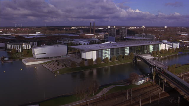 aerial of autostadt, volkswagen office park or complex. river and bridge. railroad tracks and train. factory and smoke stack in bgs. glass office buildings, towers. cities. europe. - wolfsburg lower saxony stock videos and b-roll footage
