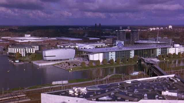 aerial of autostadt, volkswagen office park or complex. river and bridge. railroad tracks and train. factory and smoke stacks in bg. glass office buildings, towers. cities. europe. - wolfsburg lower saxony stock videos and b-roll footage