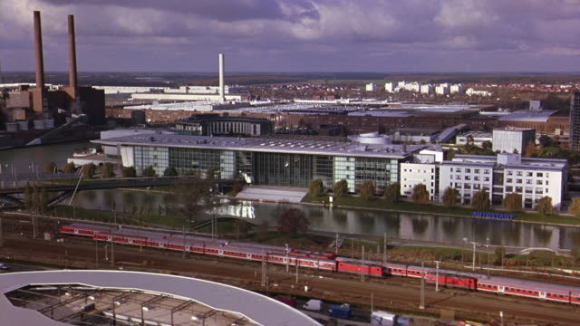 aerial of autostadt, volkswagen office park or complex. river and bridge. railroad tracks and train. factory and smoke stacks. glass office buildings, towers. cities. europe. - wolfsburg lower saxony stock videos and b-roll footage