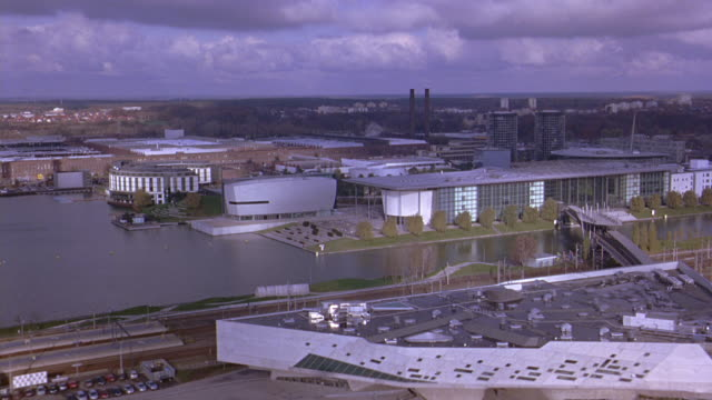 aerial of autostadt, volkswagen office park or complex and phaeno science center. river and bridge. railroad tracks and train. automobile factory and smoke stacks in bg. glass office buildings, towers. phaeno science center. cities. europe. - wolfsburg lower saxony stock videos and b-roll footage