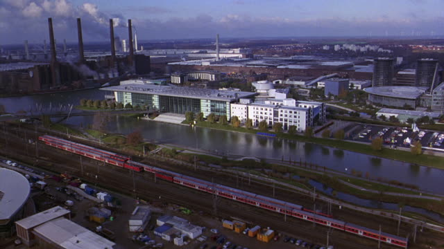 aerial of autostadt, volkswagen office park or complex. glass multi-story office buildings. cars in parking lots. automobile factory and smoke stacks. railroad tracks and train. city. river and bridge. europe. - wolfsburg lower saxony stock videos and b-roll footage
