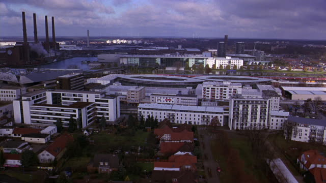 aerial of autostadt, volkswagen office park or complex. river and bridge. railroad tracks and train. automobile factory and smoke stacks in bg. multi-story houses,  apartment and office buildings. glass towers. city. europe. - wolfsburg lower saxony stock videos and b-roll footage