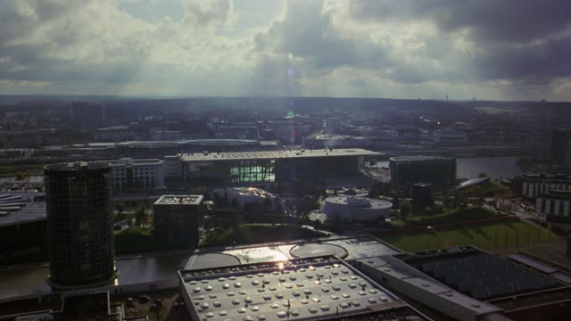 aerial of autostadt, volkswagen office park or complex. multi-story glass office buildings and towers. automobile factory and smoke stacks. railroad tracks and train. river and bridge. european city. - wolfsburg lower saxony stock videos and b-roll footage