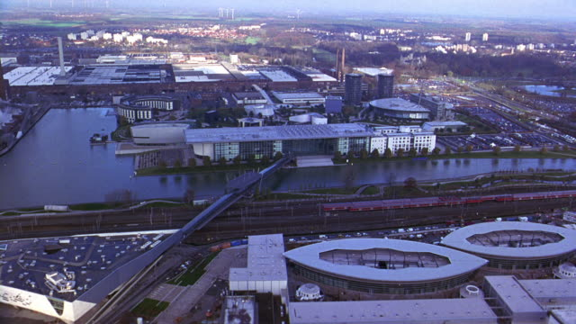 aerial of autostadt, volkswagen office park or complex. glass office buildings and towers. multi-story apartment buildings. cars in parking lots. railroad tracks and train. city. river and bridge. europe. phaeno science center. - wolfsburg lower saxony stock videos and b-roll footage
