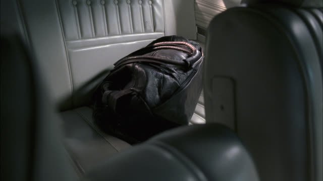 close angle of black leather bag in back seat of car. luggage or baggage. - bag stock videos & royalty-free footage