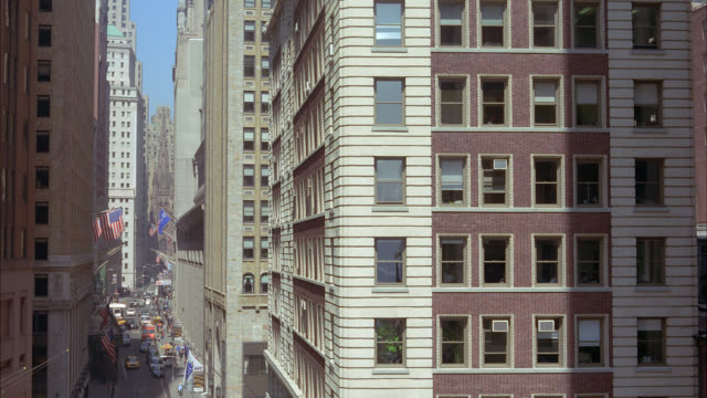 medium angle of high rise and multi-story middle class brick apartment buildings. city street below. downtown, intersection of wall and water street. - middle class stock videos & royalty-free footage