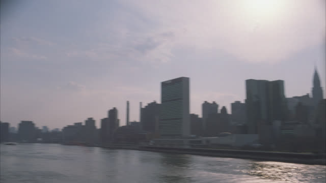 pan left to right of new york city, manhattan, skyline, along east river. midtown. united nations headquarters building, skyscrapers and high rise office or apartment buildings. brick buildings. queensboro bridge. - queensboro bridge stock videos & royalty-free footage