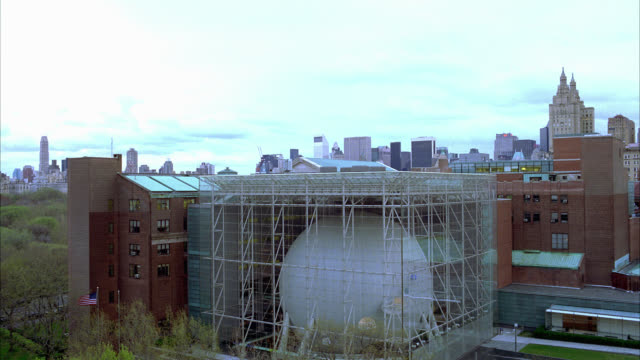 vidéos et rushes de wide angle of new york city skyline in bg, hayden planetarium at museum of natural history in fg. trees. multi-story brick building. large orb. upper west side of manhattan. - museum