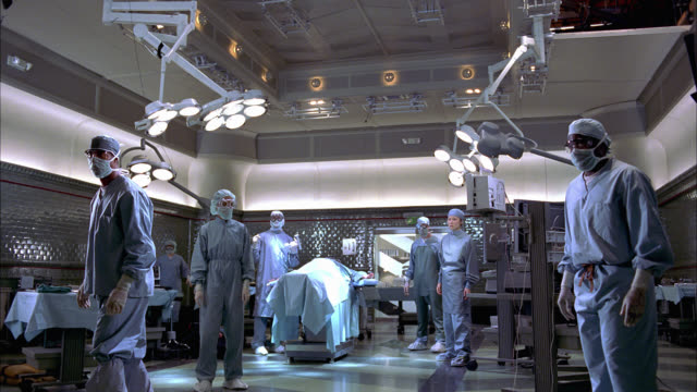 vidéos et rushes de medium angle of doctors, surgeons, nurses in operating room. medical equipment falls down, could be from explosion. emergency. sparks. stunts. - bloc