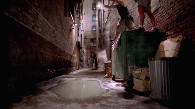 stockvideo's en b-roll-footage met medium angle of object falling into puddle of water. splash. alley between two brick apartment buildings. dumpster, trash or garbage can. - afvalcontainer container