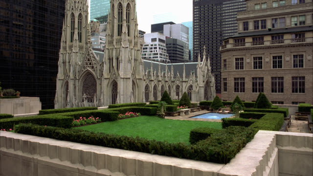 wide angle of st. patrick's church or cathedral on madison avenue. small garden with pond visible in fg. flowers and hedges. surrounding city buildings visible. citigroup or citicorp building partially visible in bg. - citigroup center manhattan stock videos & royalty-free footage