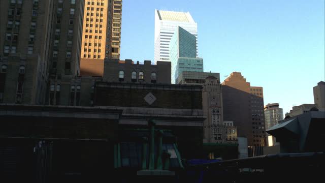 vídeos y material grabado en eventos de stock de pan up from rooftop of building and city skyline to multi-story office building. could be apartment building. cities. - piso de edificio