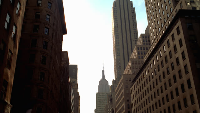 pull back from up angle of empire state building to multi-story high rise office or apartment buildings lining city street. entrances to buildings with american flags visible. cars and taxis driving on city street visible. pedestrians and construction. - ズームアウト点の映像素材/bロール