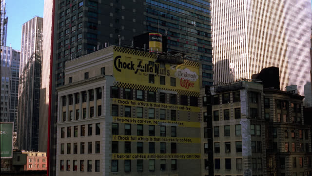 vidéos et rushes de wide angle of a building painted with a chock full o' nuts, 'the heavenly coffee,' advertisement and jingle in midtown manhattan, new york city. high rises, skyscrapers, and apartment building visible. billboards. - panneau commercial