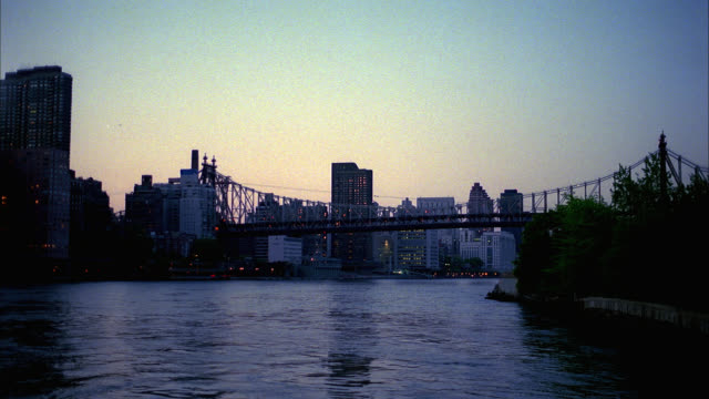 vídeos de stock e filmes b-roll de pan left to right of queensboro bridge to smallpox hospital ruins at roosevelt island. pan right to left to bridge over east river. rippling water, high rises, apartment buildings visible. could be sunset. hospitals, ruins, landmarks. - 2001