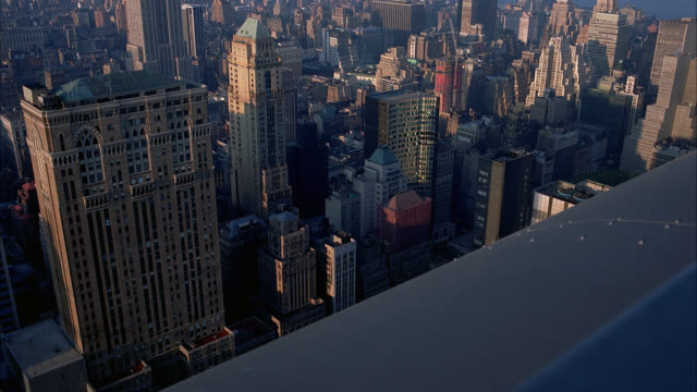 vídeos de stock e filmes b-roll de high angle down of buildings and high rises near midtown manhattan, new york. partial view of base of empire state building visible top left of clip. - 2001