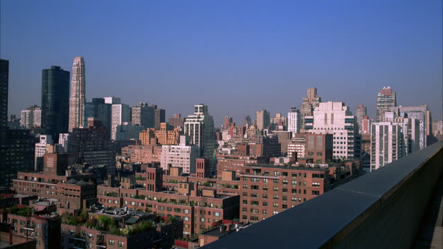 vídeos de stock e filmes b-roll de wide angle of high rises and apartment buildings in and around midtown and upper east side manhattan in new york city. clear blue skies. - 2001