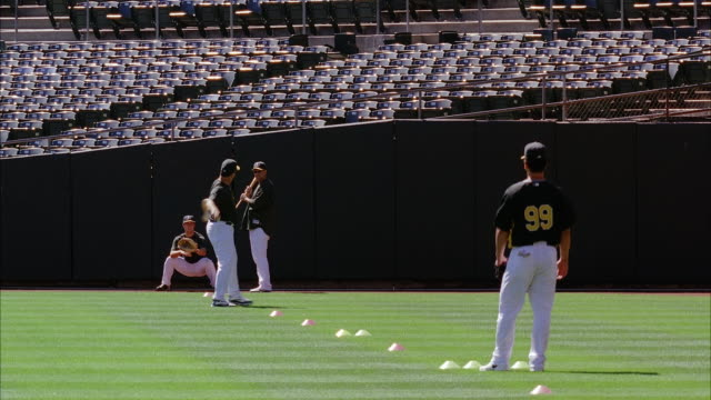 MEDIUM ANGLE OF BASEBALL PLAYERS IN UNIFORM AT OAKLAND ATHLETICS BASEBALL STADIUM. PLAYERS THROW OR TOSS BALL. COULD BE PRACTICE. STADIUM SEATS VISIBLE. CONES VISIBLE ON FIELD.