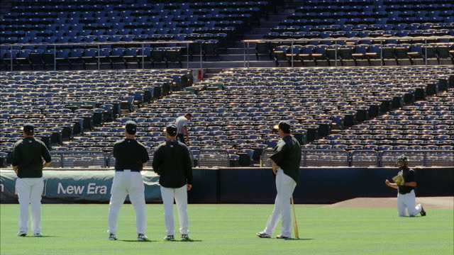 MEDIUM ANGLE OF BASEBALL PLAYERS IN UNIFORM AT OAKLAND ATHLETICS BASEBALL STADIUM. PLAYERS THROW OR TOSS BALL. COULD BE PRACTICE. STADIUM SEATS VISIBLE.