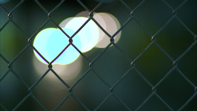 medium angle of chain-link fence. city street, underpass. street signs. cars in bg. - wire mesh fence stock videos & royalty-free footage
