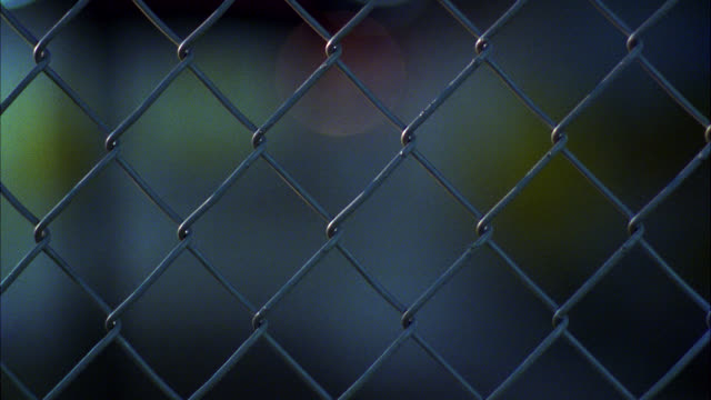 medium angle of chain-link fence. city street, underpass. street signs. - wire mesh fence stock videos & royalty-free footage