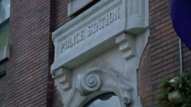 medium angle of sign above entrance to police station or precinct. brick building. - police station stock videos & royalty-free footage