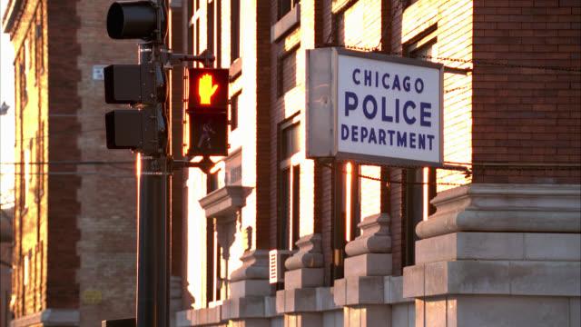 medium angle of sign for chicago police department, station, on side of brick building. crosswalk signal on street corner. - シカゴ市点の映像素材/bロール