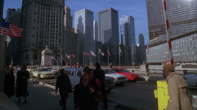 wide angle of people or pedestrians walking across michigan avenue bridge. cars driving. skyscrapers and high rise office or apartment buildings of city skyline in bg. flags. - 1998 stock videos & royalty-free footage