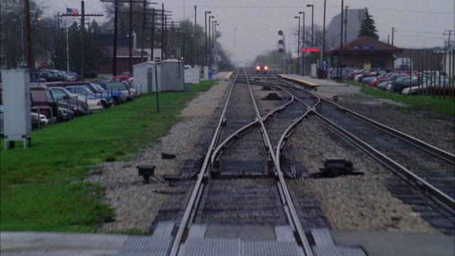 process plate straight back from train on railroad tracks. cars driving on street through railroad crossing. rain. - level crossing stock videos & royalty-free footage