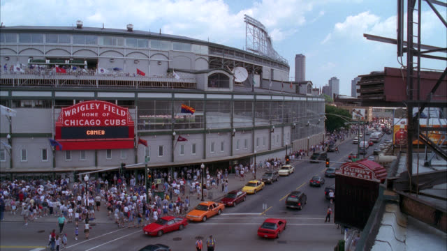vidéos et rushes de pan right to left of people, fans or spectators entering wrigley field, baseball stadium. cars on city street in fg. - chicago illinois