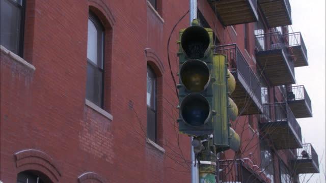 close angle of broken stoplight or traffic light. high rise brick apartment building in bg. - traffic light stock videos & royalty-free footage