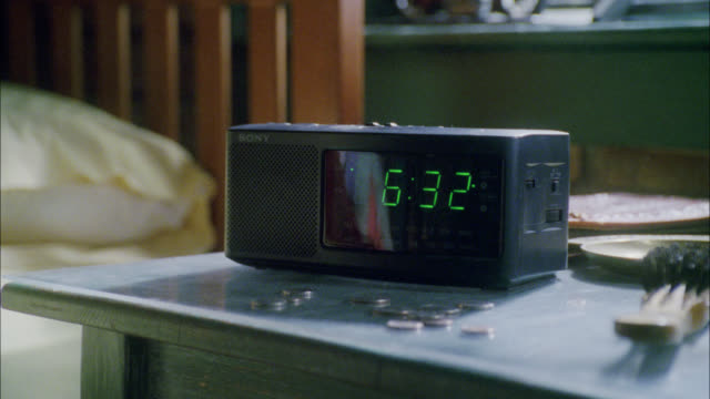pan right to left from alarm clock with digital display to empty bed. - digital clock stock videos & royalty-free footage