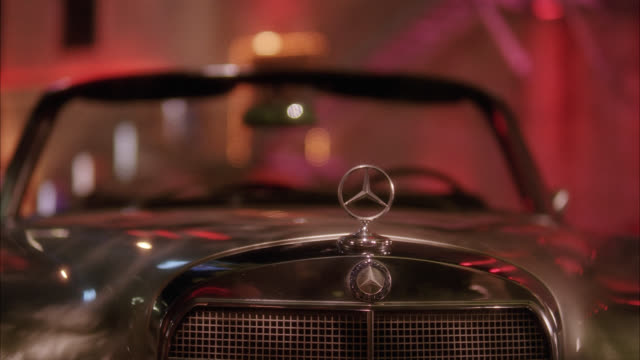 close angle of mercedes hood ornament on car. - mercedes benz markenname stock-videos und b-roll-filmmaterial