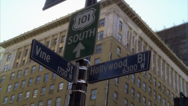 pan right to left to street sign for hollywood and vine. - segnaletica stradale video stock e b–roll