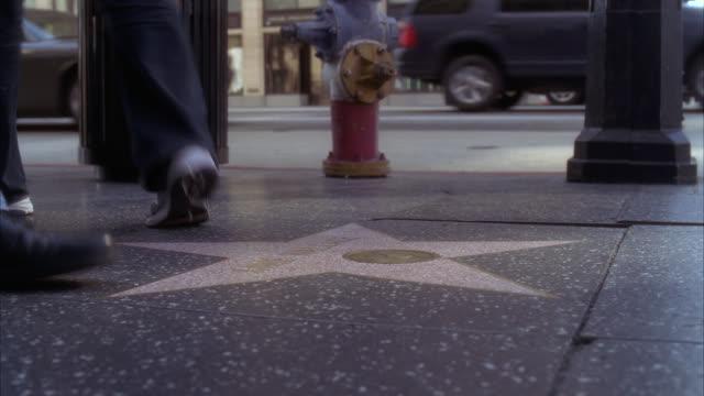 vídeos de stock e filmes b-roll de close angle of people or pedestrian's feet walking on hollywood walk of fame. landmark. hollywood and vine. - hollywood walk of fame