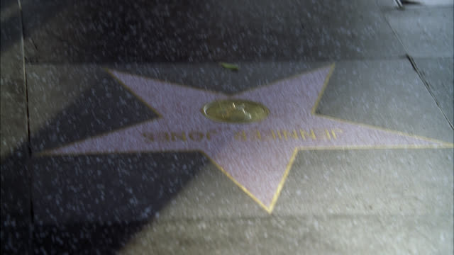 pan up from hollywood walk of fame star to people or pedestrians walking. hollywood blvd. los angeles area. landmarks. - walk of fame stock videos & royalty-free footage