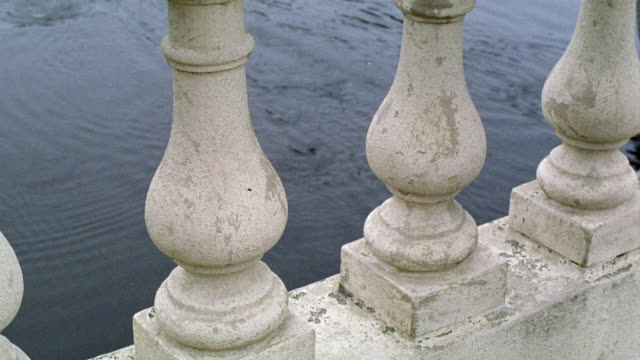 high angle down close angle through stone rungs of bridge to man on coxless pair rowing  boat in charles river below. rowing. john w. weeks bridge. - coxless rowing stock videos & royalty-free footage