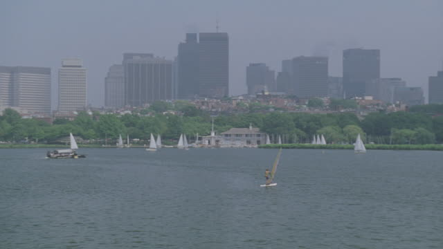 WIDE ANGLE OF BOSTON CITY SKYLINE. SAILBOATS ON CHARLES RIVER. PAN RIGHT TO LEFT TO LONGFELLOW BRIDGE OVER RIVER. WINDSURFER VISIBLE.