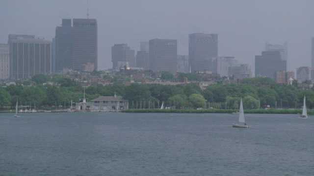 WIDE ANGLE OF BOSTON CITY SKYLINE. SAILBOATS ON CHARLES RIVER. PAN RIGHT TO LEFT TO LONGFELLOW BRIDGE OVER RIVER.
