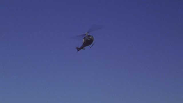 up angle of bell uh-1d military helicopter hovering or flying circles above military base. flag pole with american flag, marine flag, and american eagle. blue sky. palm trees and power or telephone wires in bg. barracks in bg. mountain or hill in bg with - hovering stock videos & royalty-free footage