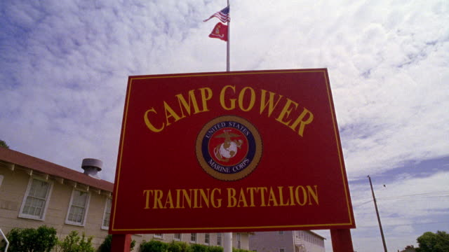 "UP ANGLE OF SIGN FOR ""CAMP GOWER TRAINING BATTALION."" MARINES EMBLEM. MARINE AND AMERICAN FLAGS ON FLAGPOLE IN BG. BLUE SKY AND CLOUDS. RANCH STYLE BUILDING IN BG COULD BE BARRACKS."