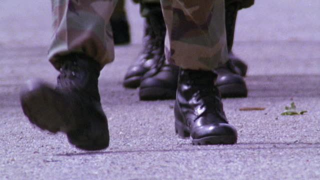 stockvideo's en b-roll-footage met close angle of boots and camouflaged legs marching on pavement or concrete. could be soldiers or military personnel. boots walk towards camera as other move in opposite direction. - leger soldaat