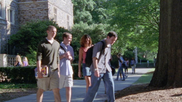 wide angle of students or people walking on college campus near brick building. duke university. ivy league. - ivy league university stock videos and b-roll footage