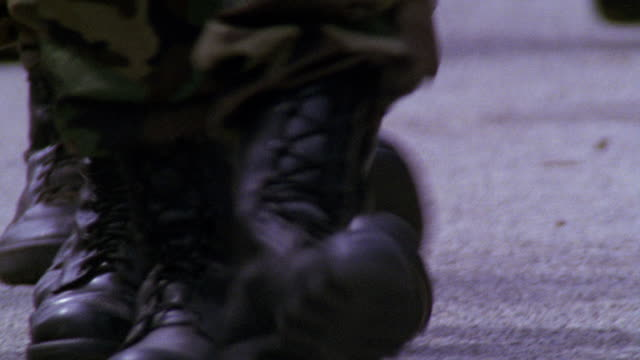 vidéos et rushes de close angle of boots and camouflaged legs marching on pavement or concrete. could be soldiers or military personnel. boots walk towards camera as other move in opposite direction. - chaussures